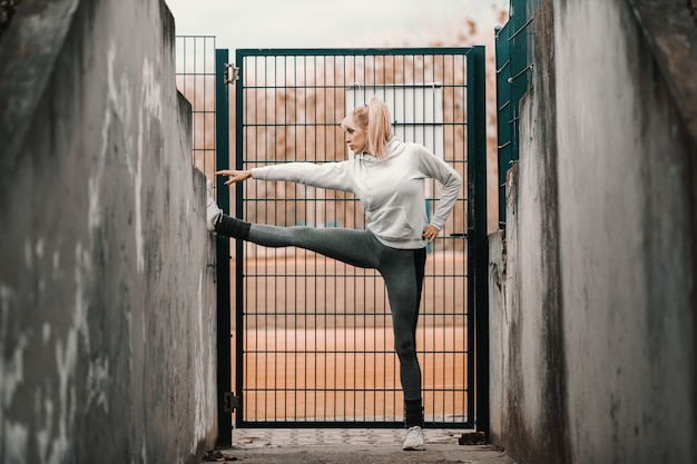 Красивый женский бегун протягивая ногу пока полагающся на стене. осенний сезон, полная длина.