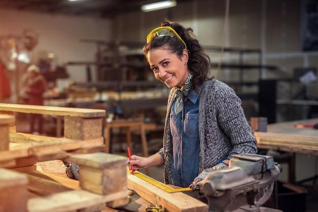 ワークショップで原木の測定を行いながらカメラを見ている中年のプロ女性大工。