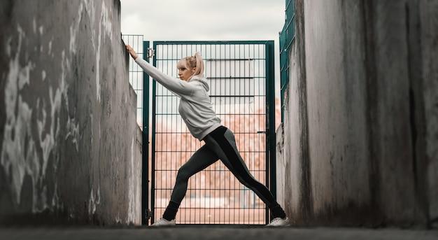 Спортивная гибкая женщина растягивает ноги, опираясь на стену перед проволочными воротами