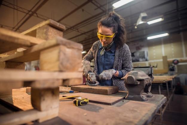 Женский плотник работая с шлифовальным прибором пока стоящ окруженный с древесиной.