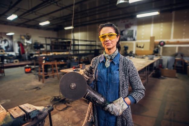Картина профессионального женского плотника, стоя в своей мастерской и проведение электродрели