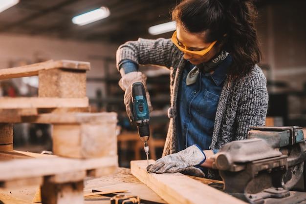 Женский плотник, используя дрель во время работы в мастерской