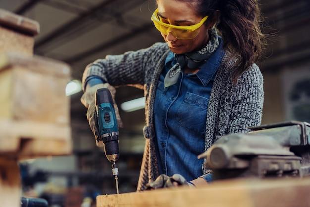 Профессиональный плотник с электрической дрелью в своей мастерской