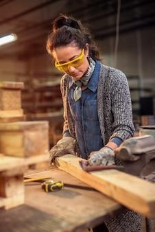Женский плотник работает с наждачной бумагой в своей мастерской