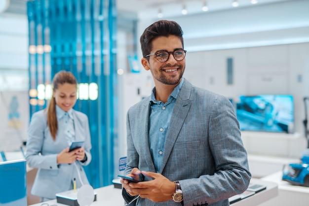 Портрет красивый мужчина, глядя в сторону в магазине технологий