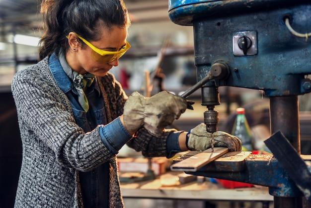 Женский плотник работая на большой электрической дрели в мастерской