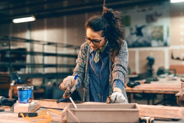 Молодая женщина красит деревянную доску на стол