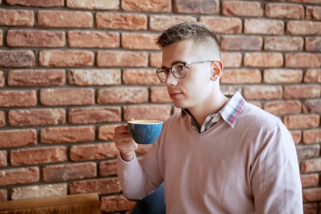 Портрет молодой привлекательный мужчина в очках одет элегантный пить кофе в кафетерии