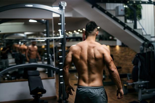 ジムでポーズをとって筋肉の上半身裸の男