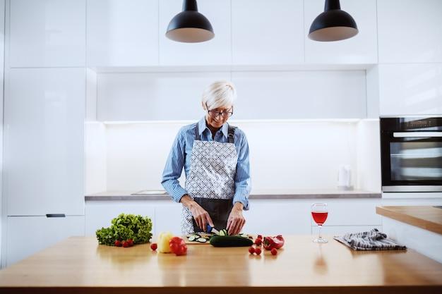 Усмехаясь старшая женщина в рисберме стоя в кухне и режа огурец