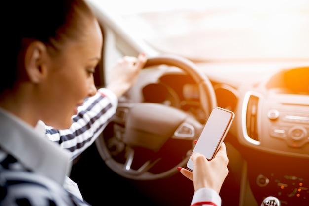 危険な状況、若い女性が車を運転して携帯電話でテキストメッセージ。