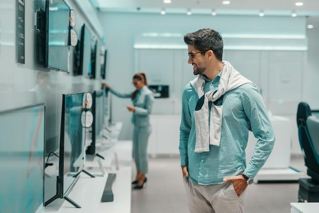 Красивый мужчина одет элегантно держась за руки в карманах и глядя на телевизор он хочет купить
