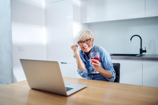 Жизнерадостная старшая женщина сидит на кухне, радуясь сумме наличных на ее счет и держа бокал вина