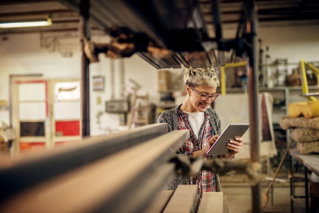ワークショップで金属パイプの背後にあるタブレットを使用して眼鏡の勤勉な短い髪の女性マネージャー