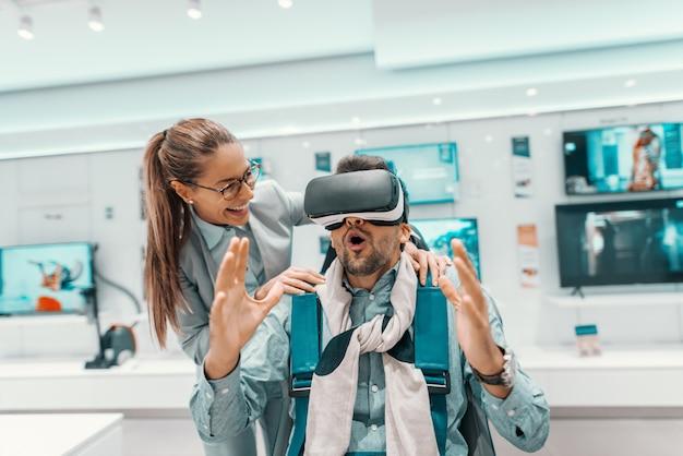 Удивленный мужчина сидит в кресле и опробует технологию рядом с женщиной