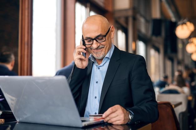Старший одет в костюм, используя смартфон и кредитную корзину для покупок в интернете