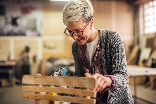 Милый плотник профессиональной женщины стоя в ее мастерской с электрической дрелью в ее руках делая деревянный стул