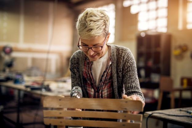 Крупным планом вид трудолюбивого профессионального плотника, стоя с электрической дрелью и делая или фиксируя стул в мастерской