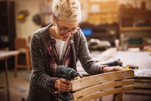 Жизнерадостная женщина плотника стоя с электрической дрелью и делая или исправляя стул в мастерской