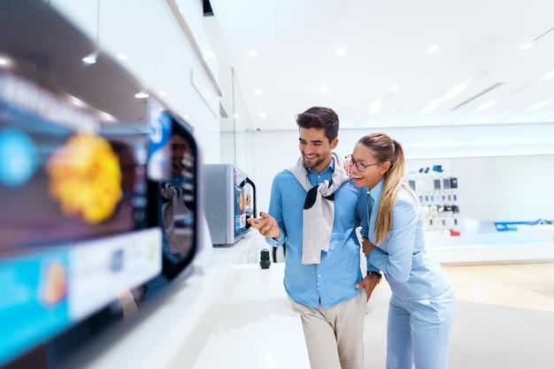 Счастливая пара ищет новую микроволновую печь в техническом магазине