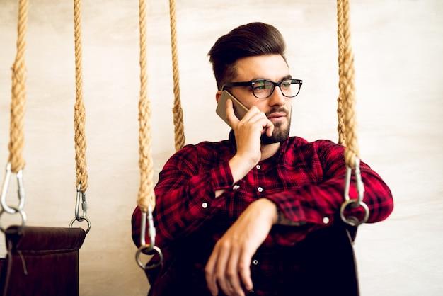 ハンサムな男が携帯電話で話しています。