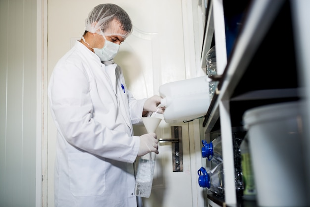 Молодой профессиональный работник в форме прозрачной жидкости из одной бутылки в другую в лаборатории.