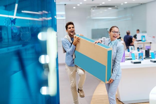 幸せな多文化のカップルはエレガントなホールディングボックスに新しいテレビを着てください。