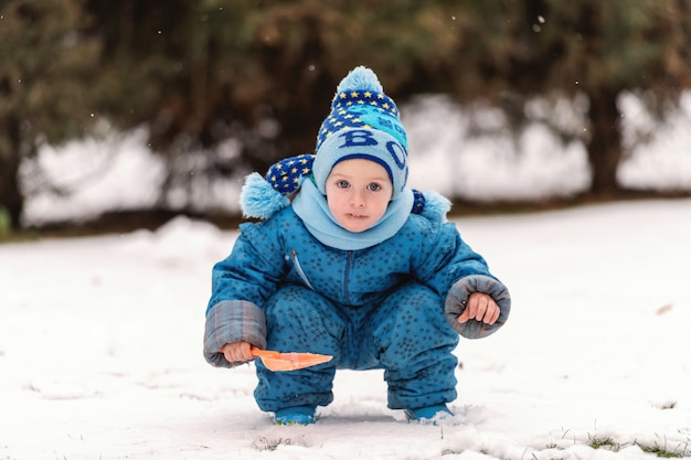 暖かい服とスカーフと帽子と小さなシャベルで雪で遊ぶかわいい白人少年。