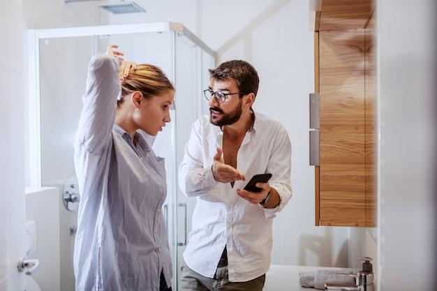 嫉妬深い白人男性がスマートフォンを押しながら彼の妻にメッセージを表示します。