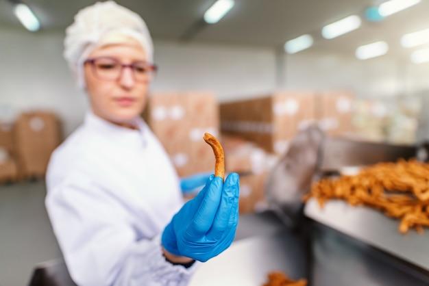 無菌の制服を着た金髪の白人女性従業員と食品工場に立っている間塩スティックを保持している青いゴム手袋のクローズアップ。