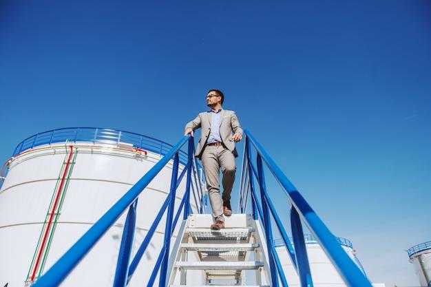 Молодой красивый кавказский бизнесмен в костюме идя вниз по лестнице и смотря его рафинадный завод.