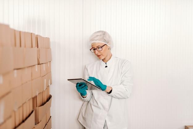 Белокурый женский работник в стерильной форме используя таблетку для логистического пока стоящ рядом с коробками в фабрике еды.