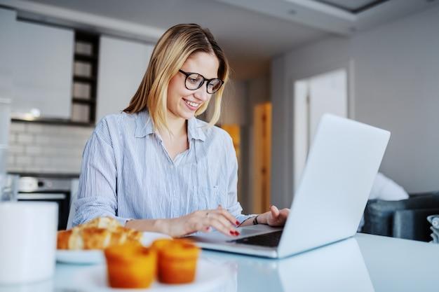 朝のダイニングテーブルに座っているとラップトップを使用して眼鏡の陽気な白人金髪女性。