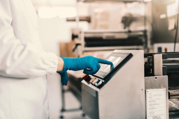 食品工場に立ちながら包装機をオンにして、滅菌のユニフォームと青いゴム手袋の若い女性従業員のクローズアップ。