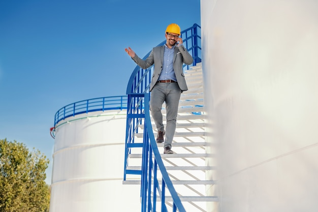 階段を下りて重要なクライアントと電話をしている頭の上のヘルメットとの訴訟で肯定的な格好良い白人実業家。製油所の外装。背景にはオイルタンクがあります。