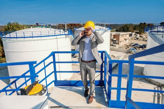 石油販売について重要なコールを持つエレガントな豊かなビジネスマン。製油所の外装。