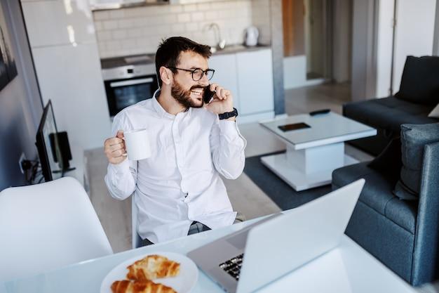 ハンサムな白人実業家は、ダイニングテーブルにカジュアルな座って、新鮮な朝のコーヒーとマグカップを押しながら電話で話している服を着ています。テーブルの上にはノートパソコンと朝食があります。