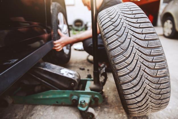 ワークショップでしゃがみながらタイヤを交換する自動車整備士。タイヤにセレクティブフォーカス。