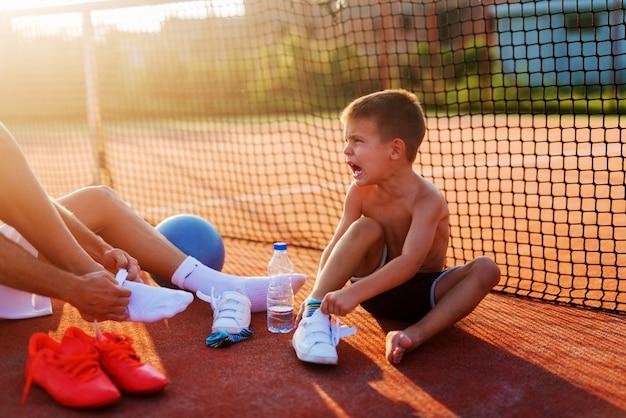 Отец и сын, принимая их носки перед тренировкой по теннису в жаркий летний день. веселятся и улыбаются.