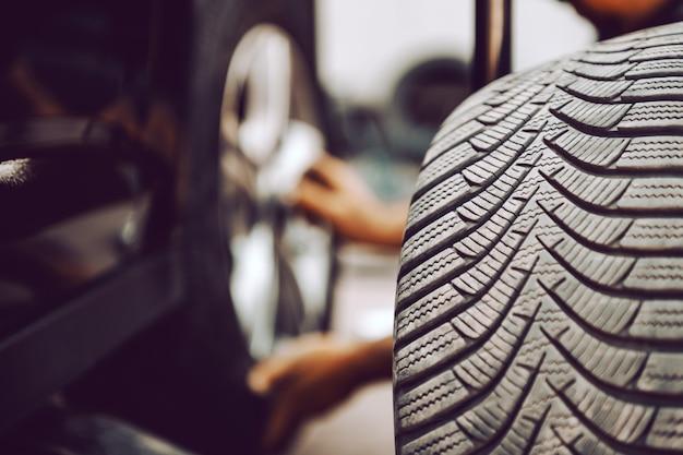 ワークショップでしゃがみながら自動車整備士のタイヤのクローズアップ。タイヤにセレクティブフォーカス。