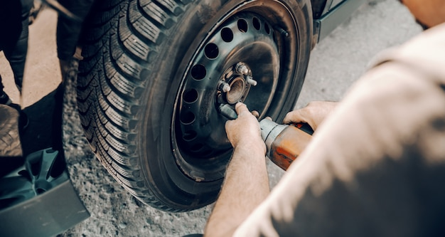 ワークショップでしゃがみながらタイヤを変更するツールを使用して自動車整備士。