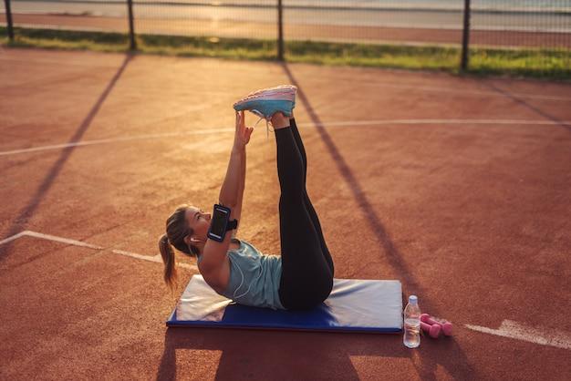 外のトレーニングフィールドでハードクランチ運動を行う強いフィット美しいやる気のあるブロンドの女の子。