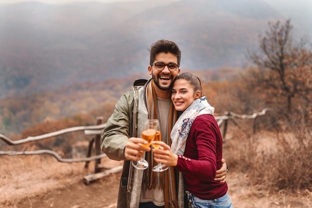 幸せなカップルを抱き締めると屋外でトーストを作ります。秋のシーズン。森と山。