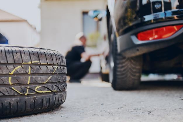 自動車整備士のワークショップで地面に古いタイヤのクローズアップ。
