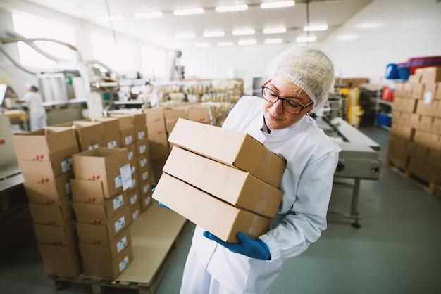 Работница в стерильной одежде поднимает тяжелые коробки на фабрике.