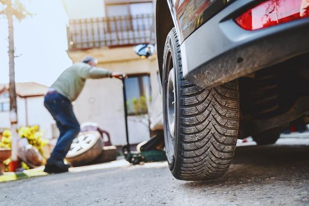 Автомеханик, используя автомобильный домкрат в мастерской. выборочный фокус в шинах.