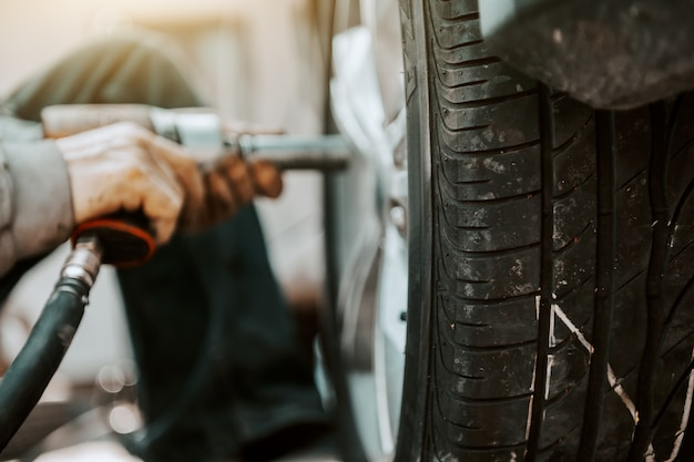 ワークショップでしゃがみながらツールを使用してタイヤを交換する自動車整備士のクローズアップ。