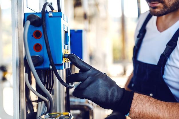 Закройте вверх красивого кавказского работника в целом и с шлемом на голове отжимая кнопку на приборной панели. добыча нефти.