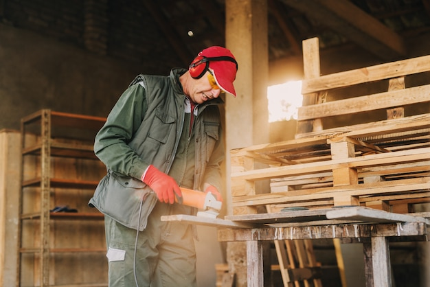 電気グラインダーを使用して木材を形作る保護ユニフォームの成熟した大工の男の写真。晴れた日に彼の作業ガレージで彼の仕事を楽しんでいます。