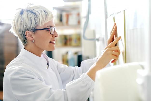 食品工場に立ちながら壁にスケジュールを読んでいる若い白人金髪女性従業員のプロフィール。
